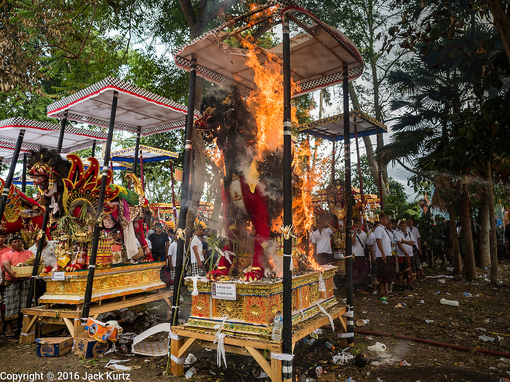16 JULY 2016 - UBUD, BALI, INDONESIA: Flames consume a sarcophagus during the mass cremation in Ubud. Local people in Ubud exhumed the remains of family members and burned their remains in a mass cremation ceremony Wednesday. Almost 100 people were cremated and laid to rest in the largest mass cremation in Bali in years this week. Most of the people on Bali are Hindus. Traditional cremations in Bali are very expensive, so communities usually hold one mass cremation approximately every five years. The cremation in Ubud concluded Saturday, with a large community ceremony.     PHOTO BY JACK KURTZ
