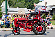 A man drives an International Harvester McCormick Farmall tractor in the Independence Day parade in Millville, Pennsylvania on July 5, 2021.
