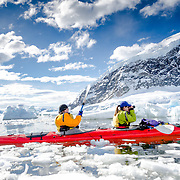 Kayakers in a tandem kayak navigate thick brash ice on the water at Neko Harbour, Antarctica.