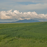 Clouds hover over the Highwood Mountains, pastures and wheat fields near Great Falls, Montana.