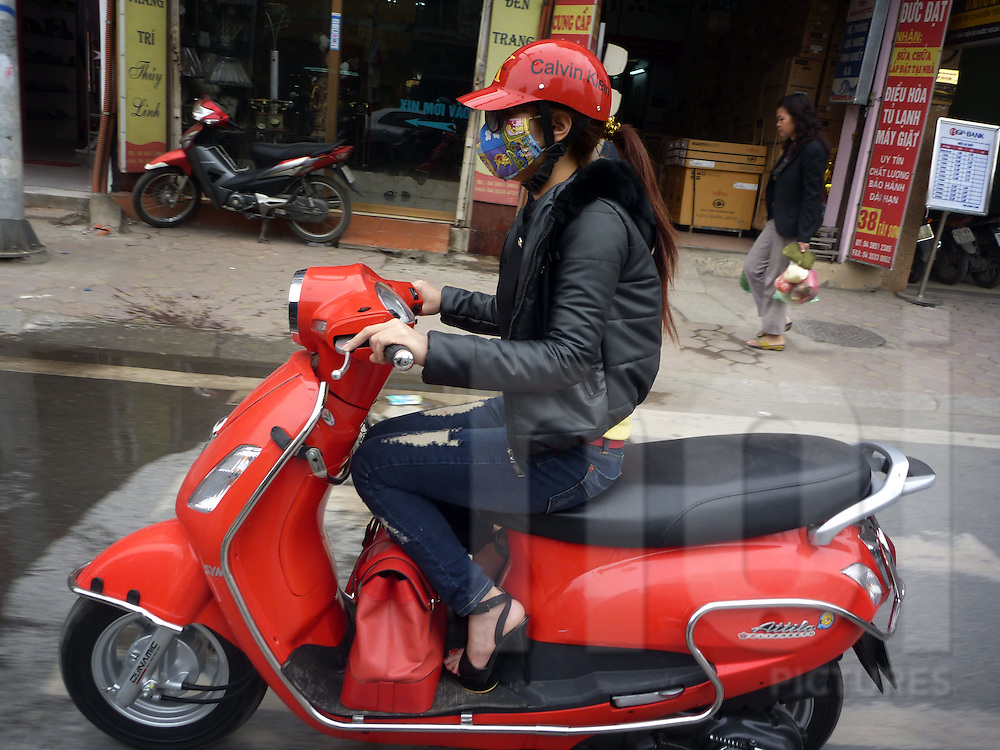 a young woman rides a red scooter in the streets of Hanoi, Vietnam. She also wears a red helmet and a red bag.