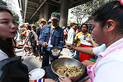 © Licensed to London News Pictures. 18/01/2014. Anti-Government protestors line up and are served free food funded by the PDRC during an anti-government street rally in Bangkok, Thailand. Anti-government protesters launch 'Bangkok Shutdown', blocking major intersections in the heart of the capital, as part of their bid to oust the government of Prime Minister Yingluck Shinawatra ahead of elections scheduled to take place on February 2. Photo credit : Asanka Brendon Ratnayake/LNP