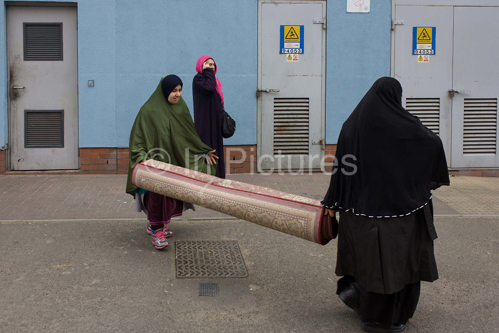 Three muslim women carry a heavy carpet along street at Elephant & Castle in Southwark, south London. Struggling with the weight of the rug, the ladies have just dropped the item before picking it up again to make their way from a nearby shop on the Walworth Road to their home nearby. Both looking to the front they progress along the street with their domestic purchase.