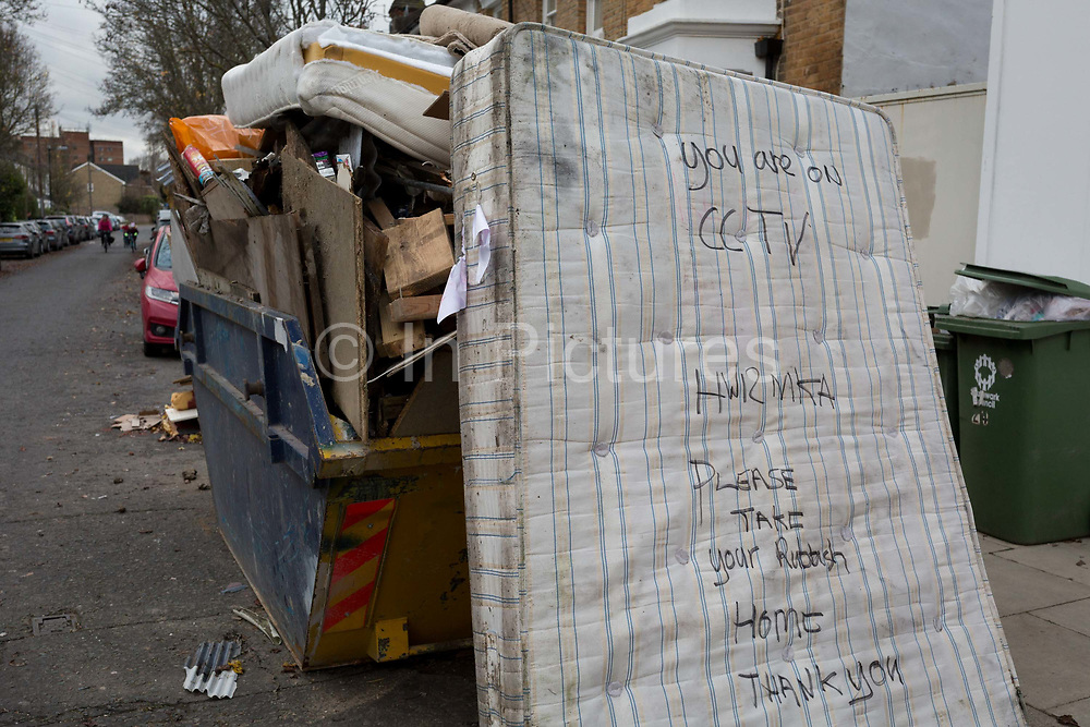 A dumped mattress next to a skip full of licensed waste, seen on a nearby shops CCTV camera which recorded the cars registration number while stopped on a residential street in East Dulwich, on 7th December 2019, in south London, England.