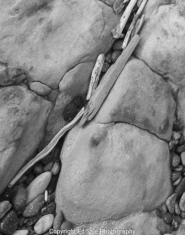 Driftwood lies between rocks on Weston Beach at Point Lobos, California