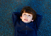 Young daydreaming Boy lies on a blue carpet looking up