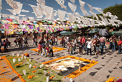 "North America, Mexico, San Miguel de Allende, people under streamers of tissue paper flags, known as ""Papel Picado""  and elaborate altars of beans and marigolds, in El Jardin plaza during Day of the Dead celebrations."