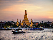 "06 MARCH 2019 - BANGKOK, THAILAND:  The sunsets on Wat Arun. Wat Arun Ratchawararam Ratchawaramahawihan or Wat Arun (""Temple of Dawn"") is a Buddhist temple (wat) in Bangkok on the Thonburi side of the Chao Phraya River. The temple derives its name from the Hindu god Aruna, who is personified as the rising sun. Wat Arun is among the best known of Thailand's temples. The temple has existed since at least the seventeenth century, but its distinctive prang (spires) were built in the Khmer style in the early nineteenth century during the reign of King Rama II.   PHOTO BY JACK KURTZ"