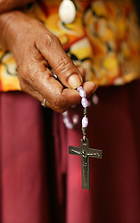 A woman is seen with rosary beads, Batticaloa, Sri Lanka, Jan. 16, 2005. Residents of the small Christian village Dutch Bar spent more than six weeks in a makeshift refugee camp at the local convent recovering from the devastating tsunami that hit the eastern and southern borders of Sri Lanka. They were then moved into another temporary living camp, while awaiting the building of new homes.