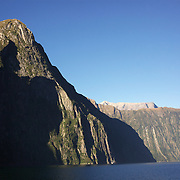 Milford Sound (Piopiotahi in M?ori) is a fjord in the south west of New Zealand's South Island, within Fiordland National Park and the Te Wahipounamu World Heritage site. It has been judged the world's top travel destination and is acclaimed as New Zealand's most famous tourist destination..Milford Sound runs 15 kilometres inland from the Tasman Sea at Dale Point - the mouth of the fiord - and is surrounded by sheer rock faces that rise 1,200 metres (3,900 ft) or more on either side. Among the peaks are The Elephant at 1,517 metres (4,977 ft), said to resemble an elephant's head and The Lion, 1,302 metres (4,272 ft), in the shape of a crouching lion. Lush rain forests cling precariously to these cliffs, while seals, penguins, and dolphins frequent the waters and whales can be seen sometimes..Milford Sound sports two permanent waterfalls all year round, Lady Bowen Falls and Stirling Falls. After heavy rain many hundreds of temporary waterfalls can be seen running down the steep sided rock faces. .The beauty of this landscape draws thousands of visitors each day, with between 550,000 and 1 million visitors in total per year. This makes the sound one of New Zealand's most-visited tourist spots, and also the most famous New Zealand tourist destination.  Milford Sound, New Zealand. 29th April 2011. Photo Tim Clayton