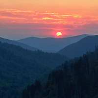 Sunset with yellow ball of sun touching horizon taken from Morton's Overlook in Smoky Mountains National Park