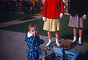 A little boy wearing a blue jump suit stands on the pavement outside his house holding the handlebars of a favourite matching blue coloured tricycle. He looks upwards towards the viewer slightly bemused about having his picture taken by his father who looks down from a standing position. Meanwhile, the boys sister towers above him dressed in a bright red coat and clean white gloves and short white socks. Alongside her is a friend also wearing gloves and a knee-length skirt but we see only their lower bodies and not their faces so they are unrecognisable - an older sibling and a girl friend. It is the summer of 1960 and while the red is vibrant, the blues and greens are more muted in this Kodachrome film which has a wonderful magenta colour cast in the mid-tones reminiscent of the classic days of early photography when shifts in color gave a faded look