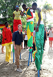Prince Harry meets stilt walkers on Grand Anse Beach in Grenada during the second leg of his Caribbean tour.