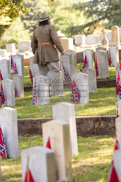 Civil war re-enactors in period costume walk past grave markers during a service at Elmwood Cemetery to mark Confederate Memorial Day May 2, 2015 in Columbia, SC. Confederate Memorial Day is a official state holiday in South Carolina and honors those that served during the Civil War.
