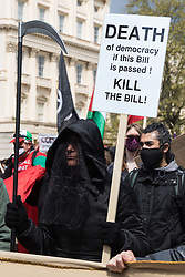 London, UK. 1st May, 2021. A man dressed as Grim Reaper joins thousands of people marching along the Mall during a Kill The Bill demonstration as part of a National Day of Action on International Workers Day. Nationwide protests have been organised against the Police, Crime, Sentencing and Courts Bill, which would grant the police a range of new discretionary powers to shut down protests.