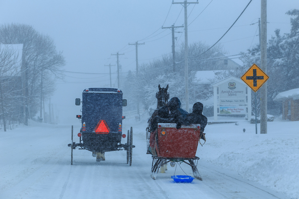 Bird-in-Hand, PA - March 5, 2015: An Amish buggy and a sleigh share the roadway during a snowstorm in rural Lancaster County.