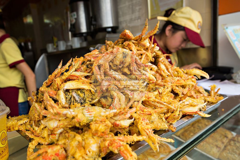 A vendor sells fried crab in Yu Gardens bazaar Shanghai, China