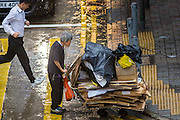 13 AUGUST 2013 - HONG KONG:  A man pushes his cart of recyclables up on to a curb during Typhoon Utor in Hong Kong. Typhoon Utor (known in the Philippines as Typhoon Labuyo) is an active tropical cyclone located over the South China Sea. The eleventh named storm and second typhoon of the 2013 typhoon season, Utor formed from a tropical depression on August 8. The depression was upgraded to Tropical Storm Utor the following day, and to typhoon intensity just a few hours afterwards. The Philippines, which bore the brunt of the storm, reported 1 dead in a mudslide and 23 fishermen missing at sea. The storm brushed by Hong Kong bringing several millimeters of rain and moderate winds to the island but causing no reported damage or injuries. It is expected to make landfall in China.  PHOTO BY JACK KURTZ