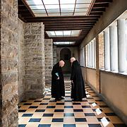 Two elderly monks are discussing in a corridor of Solesmes abbey. 04-05-16<br /> Deux moines âgés discutent dans un couloir de l'abbaye de Solesmes. 04-05-16