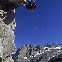 ROCK CLIMBING, Ben Wiltsie (MR) rappels off Sierra crag, John Muir Wild. (CA). Palisade Glacier bkg.