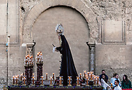 A paso carrying the Virgin Mary is passing in front of the Mezquita, the Cathedral of Cordoba. Andalusia, Spain.