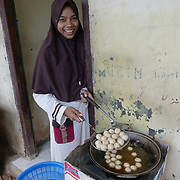 A young muslim girl fixing deep fried chicken balls on the porch of her home in Komodo Village. Komodo Island, Indonesia.