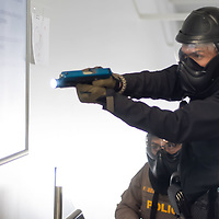 Two Navajo Nation police officers make their way up to the second floor of the fitness center at the Tséhootsooí Medical Center, as part of the active shooter training exercise, in Window Rock on Thursday.