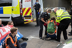 Godstone, UK. 13th September, 2021. Surrey Police officers arrest an Insulate Britain climate activist who had blocked a slip road from the M25 as part of a new campaign intended to push the UK government to make significant legislative change to start lowering emissions. The activists, who wrote to Prime Minister Boris Johnson on 13th August, are demanding that the government immediately promises both to fully fund and ensure the insulation of all social housing in Britain by 2025 and to produce within four months a legally binding national plan to fully fund and ensure the full low-energy and low-carbon whole-house retrofit, with no externalised costs, of all homes in Britain by 2030 as part of a just transition to full decarbonisation of all parts of society and the economy.