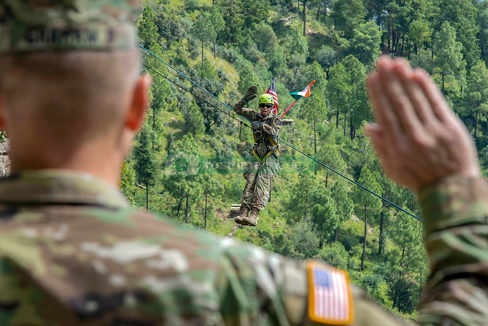 Spc. Sierra Hill, a Soldier with 1-2 Stryker Brigade Combat Team, takes the oath of enlistment on a zipline at Chaubattia Military Station, India, Sept. 25, 2018. The reenlistment ceremony was administered by Maj. Gen. William Graham, the I Corps deputy commanding general, during Exercise Yudh Abhyas 18. (U.S. Army photo by Staff Sgt. Samuel Northrup)