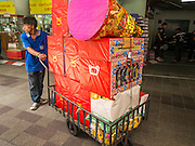 """10 AUGUST 2014 - BANGKOK, THAILAND: A volunteer pushes a cart full of joss paper to be burned in a merit making for Ghost Month at the Poh Teck Tung Shrine in Bangkok. The seventh month of the Chinese Lunar calendar is called """"Ghost Month"""" during which ghosts and spirits, including those of the deceased ancestors, come out from the lower realm. It is common for Chinese people to make merit during the month by burning """"hell money"""" and presenting food to the ghosts.     PHOTO BY JACK KURTZ"""