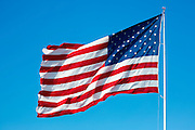 Stars and Stripes American flag blowing in the wind from flagpole on blue sky day in USA