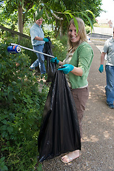 Woman using litter picking tongs to collect rubbish,
