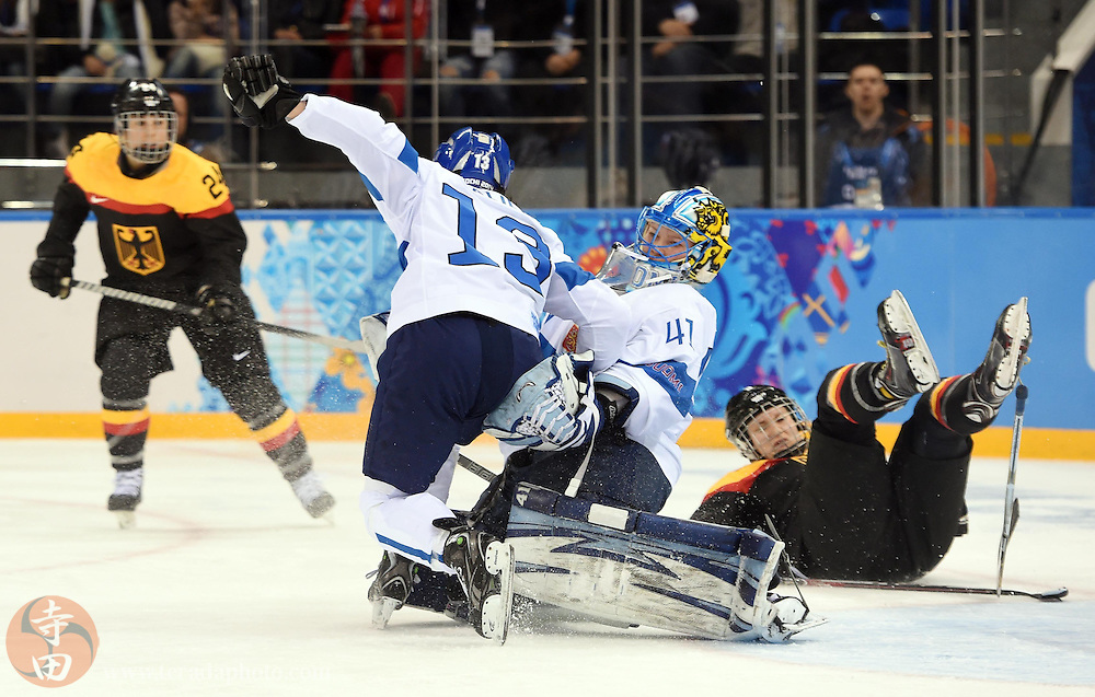 Feb 16, 2014; Sochi, RUSSIA; Finland forward Rikka Valila (13) collides with goalkeeper Noora Raty (41)  in the women's ice hockey classifications round against Germany during the Sochi 2014 Olympic Winter Games at Shayba Arena.