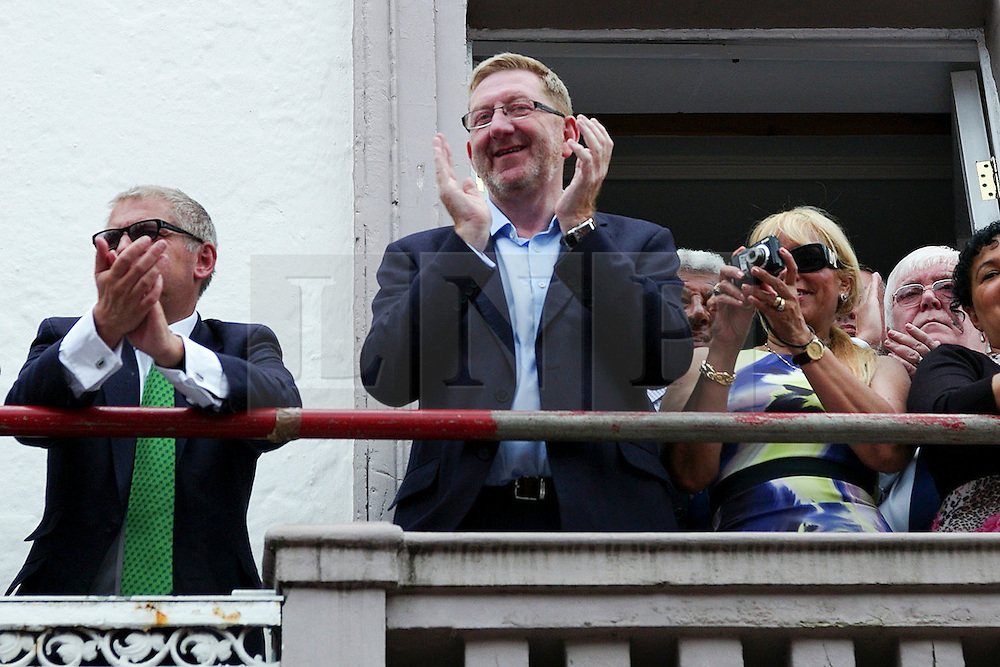 """© Licensed to London News Pictures. 13/07/2013<br /> <br /> Durham City, England, United Kingdom<br /> <br /> General Secretary of the Unite union, Len McCluskey applauds during the Durham Miners Gala as colliery bands make their way past the County Hotel.<br /> <br /> The Durham Miners' Gala is a large annual gathering held each year in the city of Durham. It is associated with the coal mining heritage of the Durham Coalfield, which stretched throughout the traditional County of Durham, and also gives voice to miners' trade unionism. <br /> <br /> Locally called """"The Big Meeting"""" or """"Durham Big Meeting"""" it consists of banners, each typically accompanied by a brass band, which are marched to the old Racecourse, where political speeches are delivered. In the afternoon a Miners' service is held in Durham Cathedral <br /> <br /> Photo credit : Ian Forsyth/LNP"""