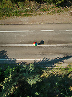 Aerial view of person holding rainbow umbrella on empty road