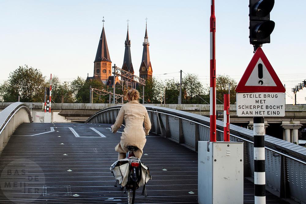 In Amsterdam worden fietsers gewaarschuwd voor een steile brug, waar aan het einde een scherpe bocht volgt.<br /> <br /> In Amsterdam a sign is warning cyclists for a steep bridge with on the end a sharp corner to the right.