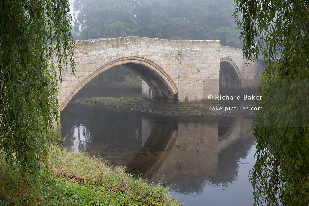 The river Coquet passes beneath the two spans of the 14th century medieval Warworth old Bridge, on a misty autumnal morning, on 26th September 2017, in Warkworth, Northumberland, England. Warkworth is a village in Northumberland, England. It is probably best known for its well-preserved medieval castle, church and hermitage.