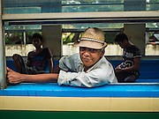 26 OCTOBER 2015 - YANGON, MYANMAR:  A man rides the Yangon Circular Train at the Pa Ywet Kone Station. The Yangon Circular Railway is the local commuter rail network that serves the Yangon metropolitan area. Operated by Myanmar Railways, the 45.9-kilometre (28.5mi) 39-station loop system connects satellite towns and suburban areas to the city. The railway has about 200 coaches, runs 20 times daily and sells 100,000 to 150,000 tickets daily. The loop, which takes about three hours to complete, is a popular for tourists to see a cross section of life in Yangon. The trains run from 3:45 am to 10:15 pm daily. The cost of a ticket for a distance of 15 miles is ten kyats (~nine US cents), and for over 15 miles is twenty kyats (~18 US cents).    PHOTO BY JACK KURTZ