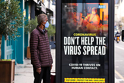 © Licensed to London News Pictures. 18/01/2021. London, UK. A man wearing a protective face covering looks at the government's 'Don't Help The Virus Spread' publicity campaign poster in north London, after the mutated variant of the SARS-Cov-2 virus continues to spread around the country. People in England aged 70 and over have started to receive offers of a coronavirus vaccine from today. The government could lift the lockdown in March, after people aged 70 and above have been vaccinated. Every adult in the UK will be offered a first dose of a coronavirus vaccine by September. Photo credit: Dinendra Haria/LNP