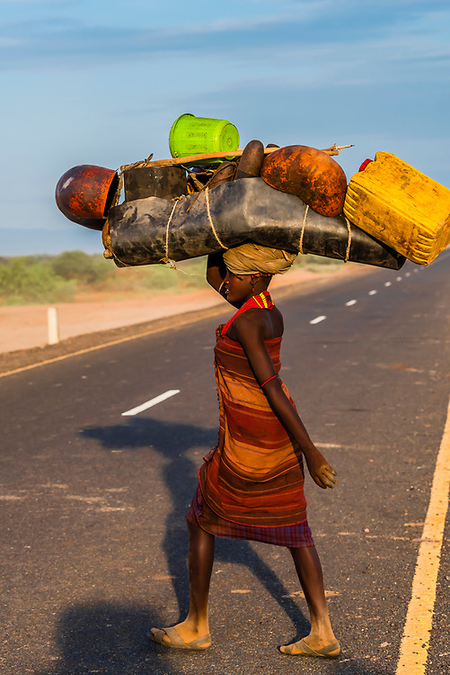Nomadic Dassanach tribe people on the move, Omo Valley, Ethiopia. They carry their campsite and everything else they need right on their heads.