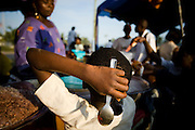 A young girl holds her spoon as she waits for her order to be ready at a small kiosk selling food during the annual Oguaa Fetu Afahye Festival in Cape Coast, Ghana on Saturday September 6, 2008.