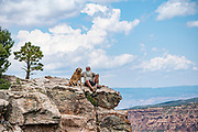 Ryan Anderson sits with his dog, Quoia,  atop a high ridge overlooking Bull Canyon and Fisher Mesa in the La Sal Mountains in Southeast Utah