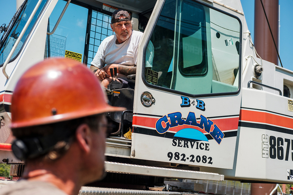 Greg Gentry, left, and Gene McDowell of B&B Crane, sitting in the crane, listen during a safety briefing prior to a lift while technicians from Lamar Advertising install a digital billboard structure along Wards Road in Lynchburg, VA Wednesday, August 29, 2018. U.S. companies are investing in re-training efforts to fill a slew of open positions as a tight labor market and changing job requirements makes it hard to find qualified staffers.<br /> CREDIT: Justin Ide for The Wall Street Journal<br /> RETRAIN