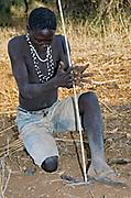 Hadzabe bushman making up fire with sticks. Lake Eyasi, northern Tanzania.