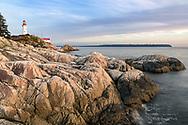 The rocky shoreline and the Point Atkinson Lighthouse at Lighthouse Park in West Vancouver, British Columbia, Canada.   Photographed from West Beach. English Bay/Burrard Inlet and Point Grey, and UBC (Vancouver) are in the background. The Point Atkinson Lighthouse was constructed in 1912 and is a National Historic Site in Canada.