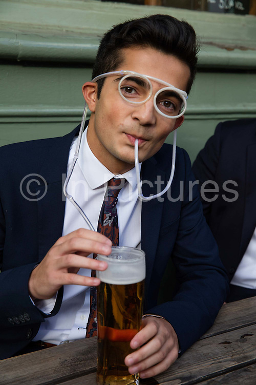 Young man drinking beer outside a London pub through a novelty straw in the shape of spectacles.