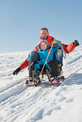 Father and daughter sledging down hill, smiling, Bavaria, Germany
