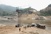 A new road bridge is currently under construction by the China Road Bridge Corporation over the Mekong river where it borders Oudomxay and Sayaboury provinces, Pak Beng, Lao PDR. Meanwhile passengers leave a rickety car ferry which takes local people and their motorbikes, cars and lorries, backwards and forwards across the river.