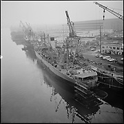 """ackroyd-P171-09. """"SS Red Oak Victory. February 10, 1966"""" (at Northwest Marine Iron Works on Swan Island. They had a contract for drydocking , bottom work, opening up lines and machinery preparation - see Oregonian January 21, 1966 pg. 42). (USS Red Oak Victory, AK235, commissioned in December, 1944, is the only World War II Victory Ship built by the Kaiser Shipyards that is restored. The ship saw service in World War II, Korea and Vietnam. In 1996, by an Act of Congress, title to the SS Red Oak Victory was conveyed to the Richmond Museum Association (Richmond Museum of History).  (Ship discharging oily waste into river. paint platform at end of ship on water.)"""