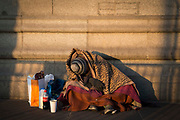 Commuters walk past a homeless man wrapped in a few blankets sleeps sitting up with his belongings as the sunrises on Tower Bridge, London. United Kingdom.